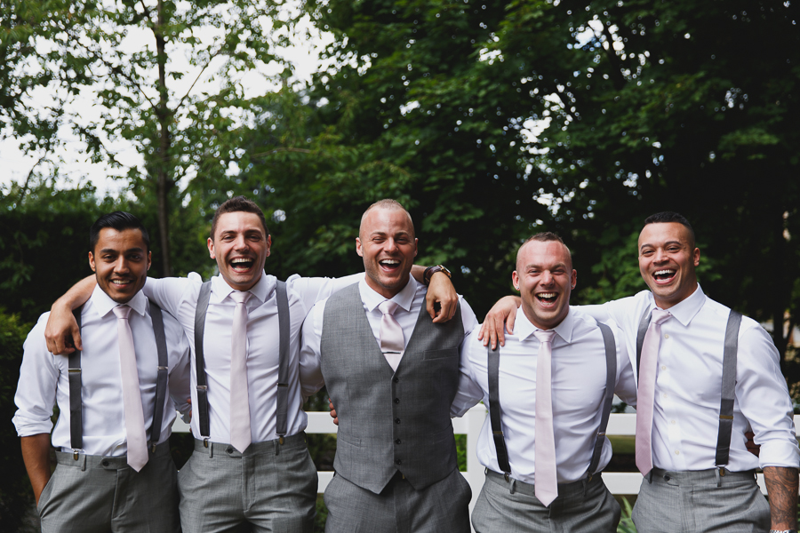 groom laughing with groomsmen in grey suits with suspenders and light pink ties