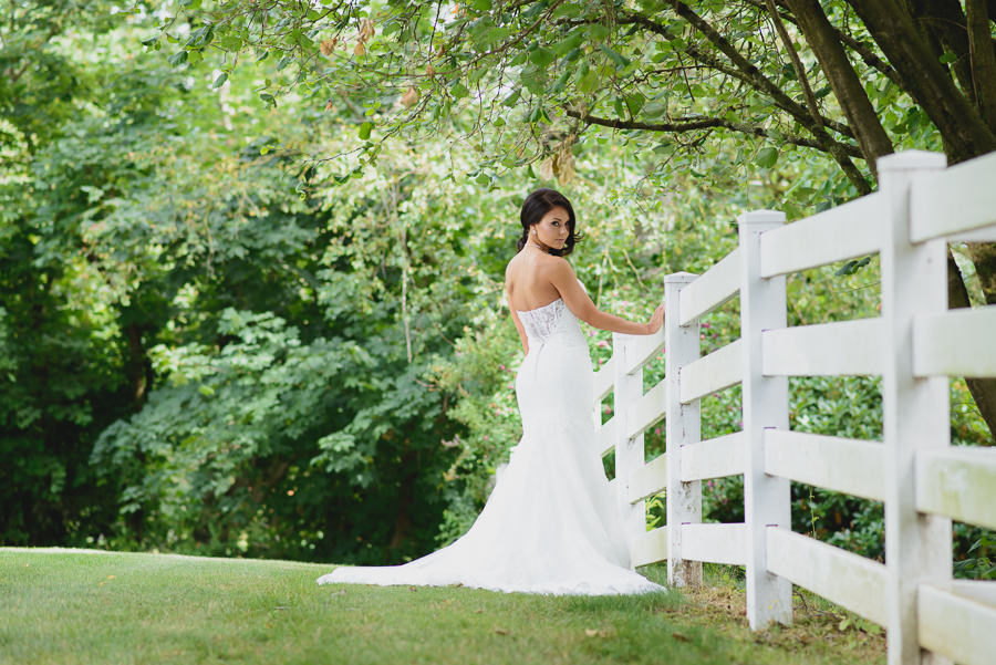 bride in sweetheart neckline lace fit and flare dress with beaded belt next to white picket fence