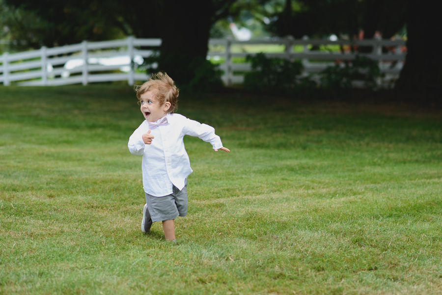 ring bearer in purple bow tie running in grass at wedding ceremony