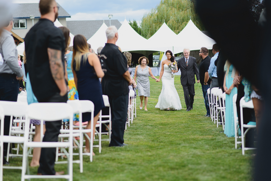 bride in lace fit and flare dress coming down the aisle at family farm wedding