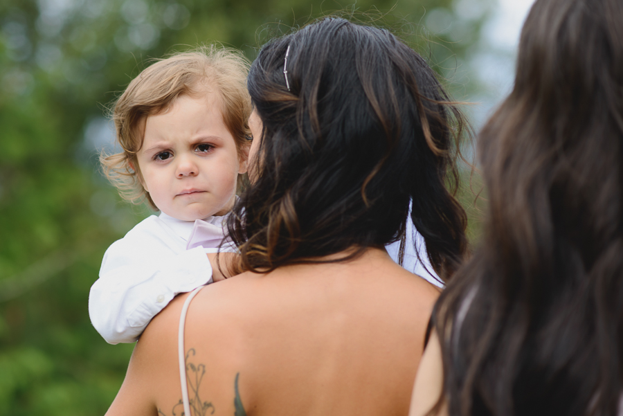 ring bearer crying and being held by maid of honour during wedding ceremony