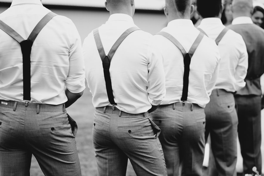 groomsmen wearing grey pants, white shirts, and suspenders during wedding ceremony