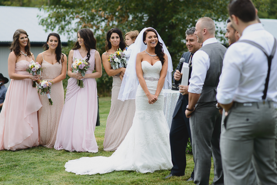 bride in lace fit and flare dress with sweetheart neckline and beaded belt and veil laughing during wedding ceremony