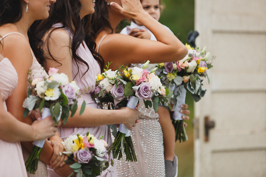 bridesmaids with mismatched pink bridesmaid dresses and rustic pink, purple, and white bouquets during wedding ceremony