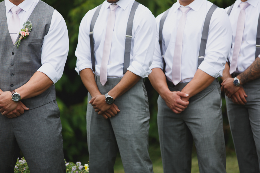groom and groomsmen wearing grey pants, white shirts, and light pink ties with suspenders during wedding ceremony