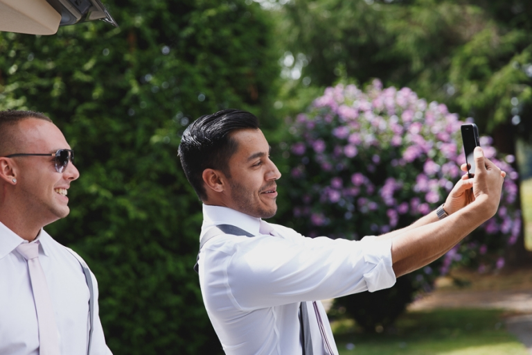 groomsmen taking a selfie before wedding ceremony
