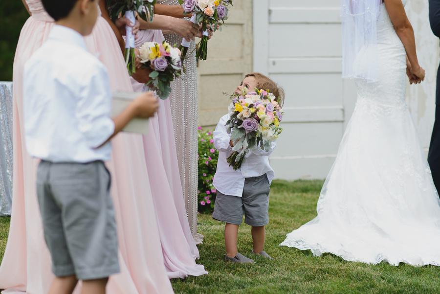 ring bearer holding rustic pink, purple, and white bouquet and looking up at bridesmaids during wedding ceremony