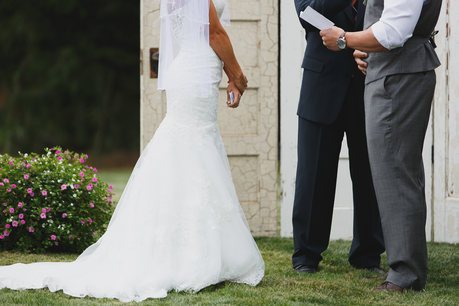 bride in lace fit and flare dress holding her vows and listening to groom read his vows