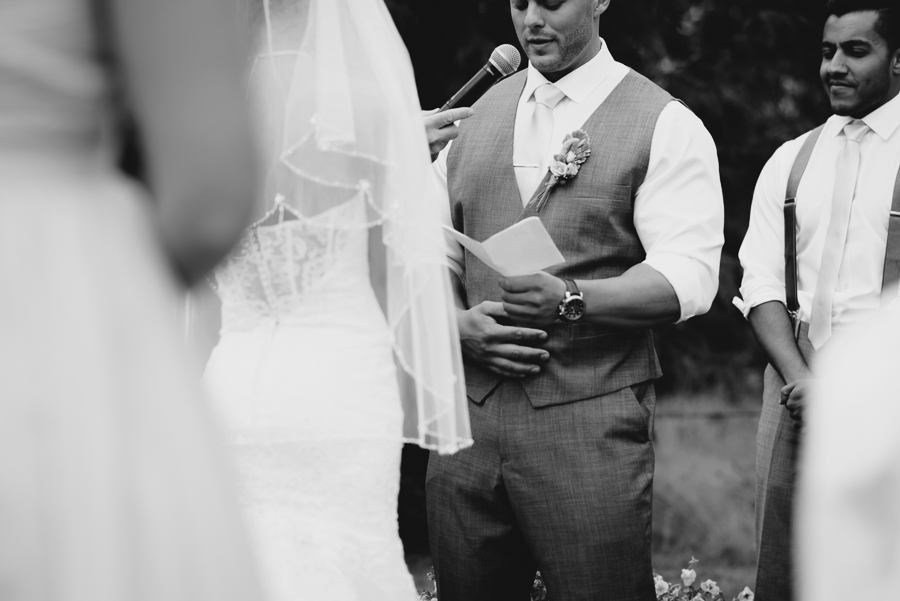 groom in grey suit and rustic boutonniere reading his vows to his bride