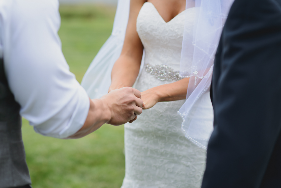 groom putting ring on bride's finger | bride wearing lace sweetheart neckline wedding dress with beaded belt