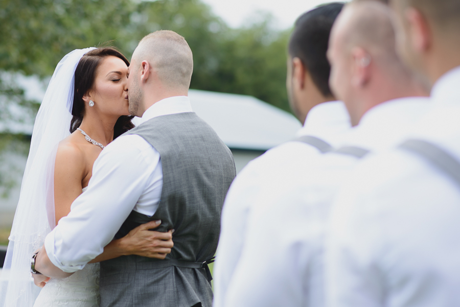 first kiss between bride in lace dress with veil and groom in grey vest and white shirt