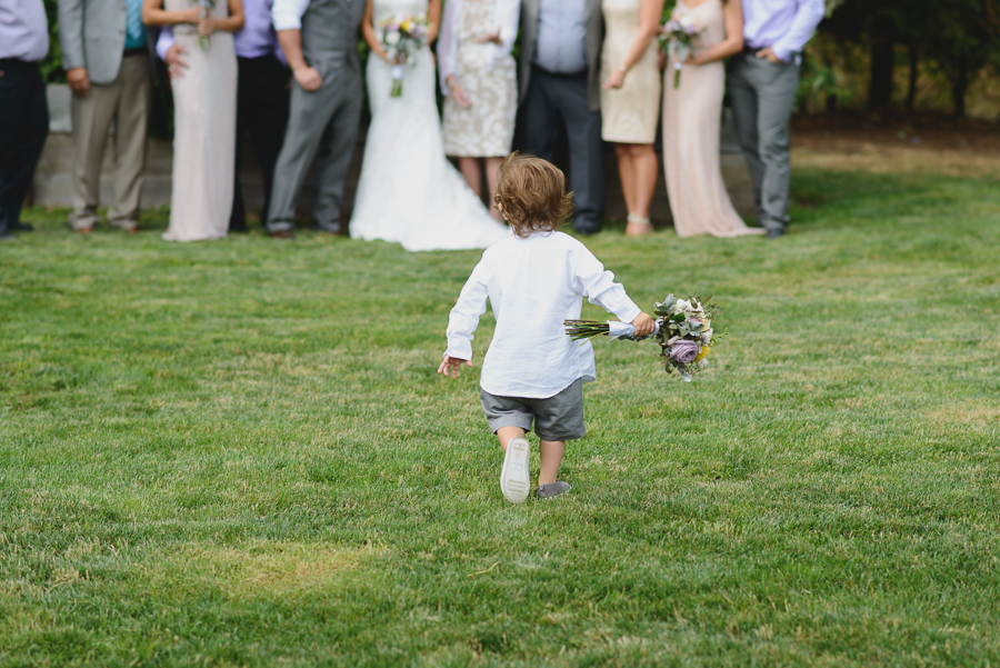 ring bearer running away with bouquet during family portraits after wedding ceremony