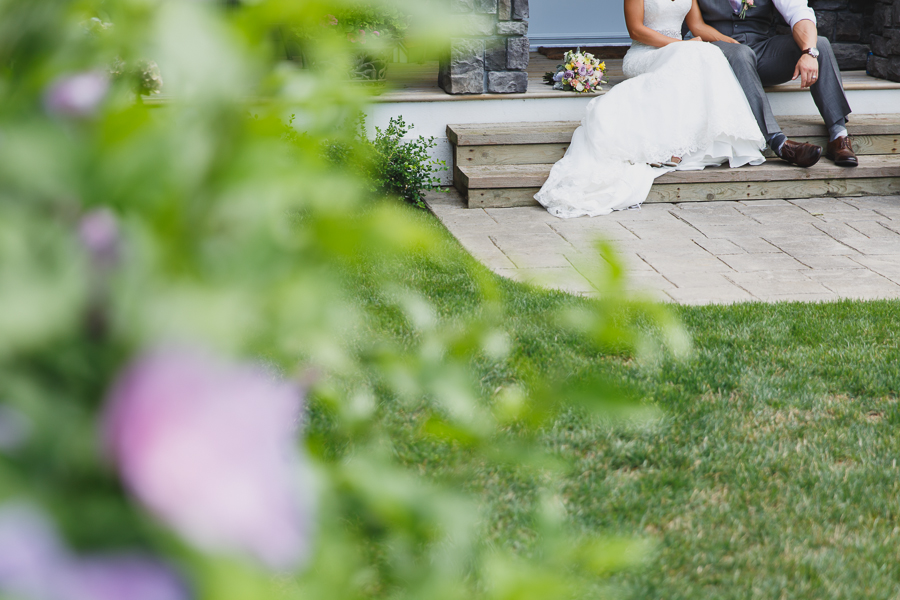 bride in lace fit and flare dress and groom in grey vest with light pink tie sitting on porch