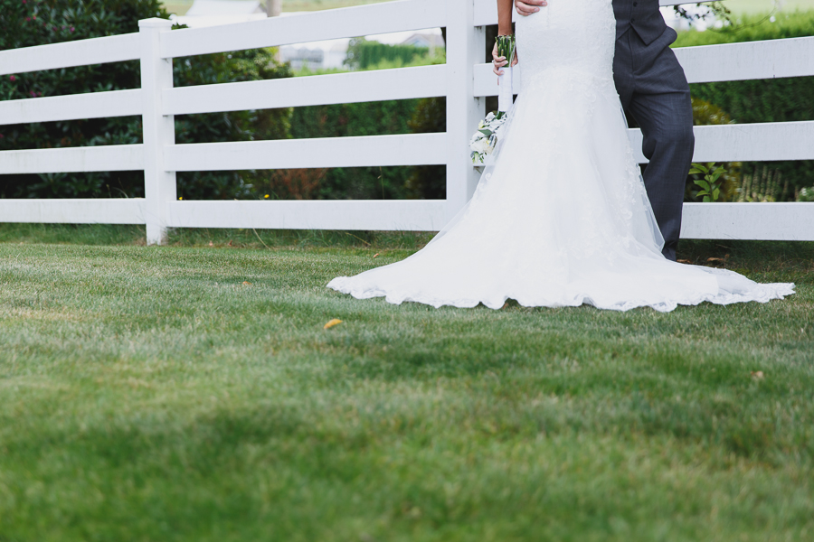 bride in lace fit and flare dress kissing groom in grey vest with light pink tie next to white picket fence