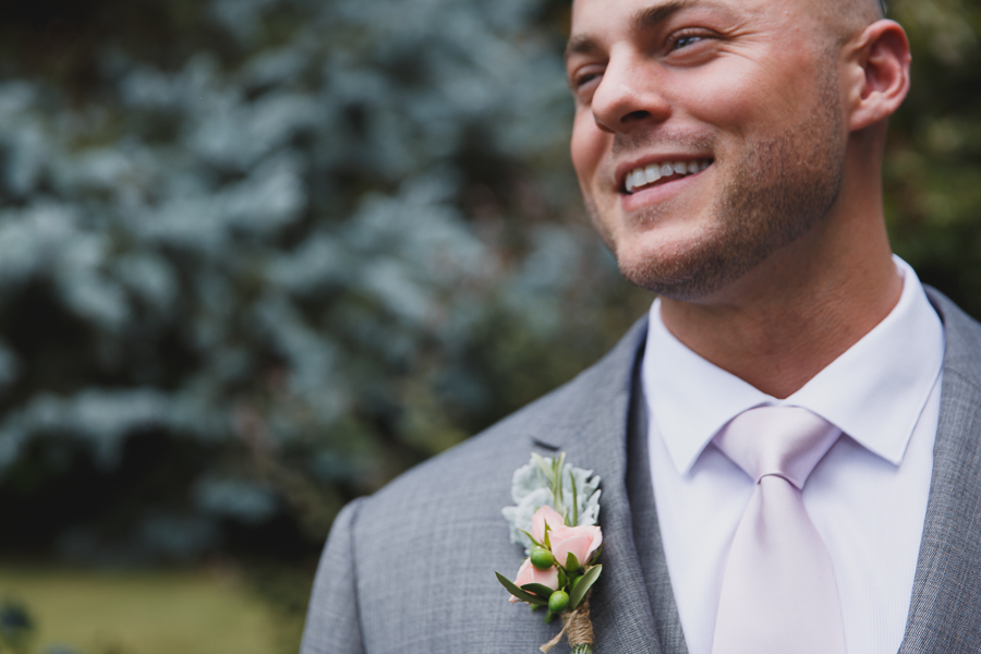groom with gray suit and rustic pink and green boutonniere with twine