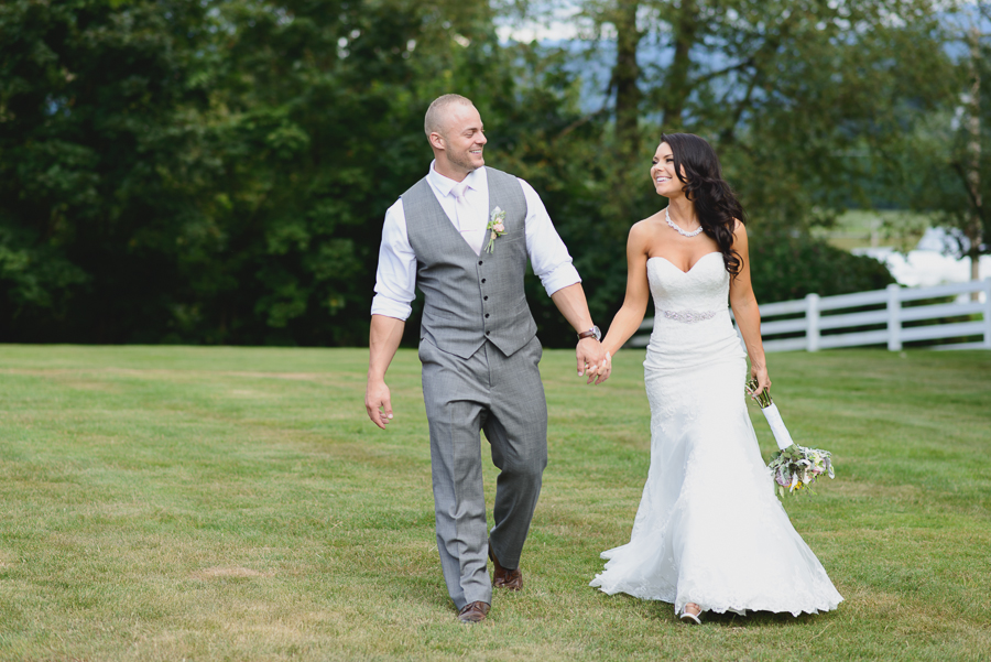 bride in lace fit and flare dress with beaded belt and rustic bouquet and groom in grey vest with light pink tie walking in field