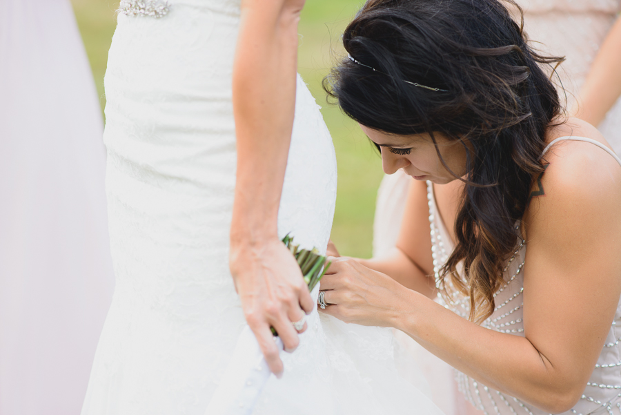 bridesmaid helping bride with bustle on wedding dress