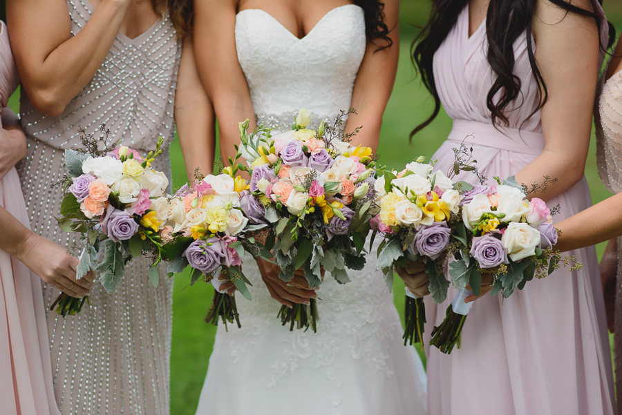 bride in sweetheart neckline lace fit and flare dress with bridesmaids in mismatched pink bridesmaids dresses with rustic pink, purple, and white bouquets with greenery and foliage