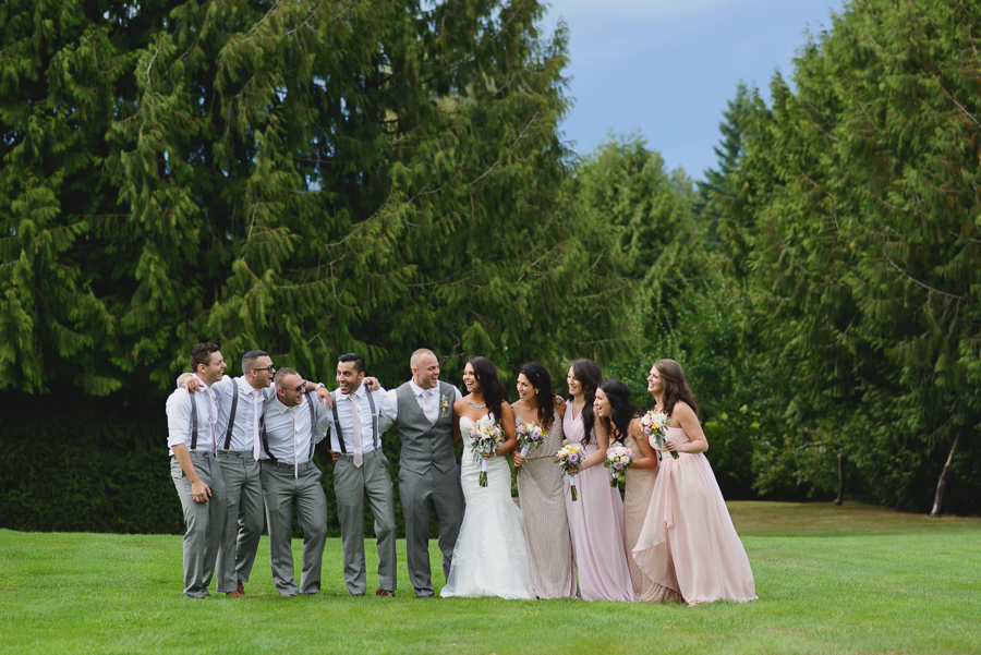 wedding party laughing | groom with groomsmen in grey suits with suspenders and light pink ties and bride in sweetheart neckline lace fit and flare dress with bridesmaids in mismatched pink bridesmaids dresses with rustic pink, purple, and white bouquets with greenery and foliage