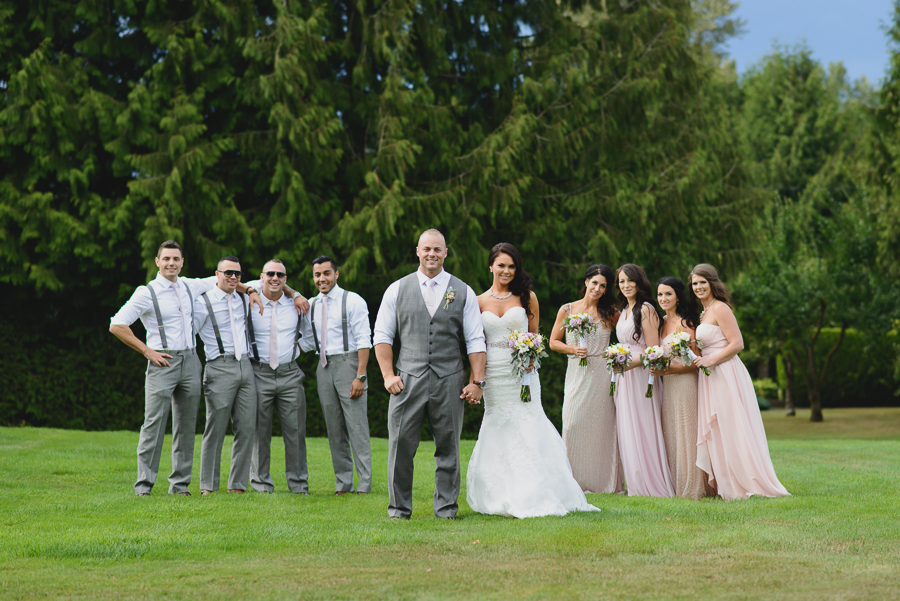 groom with groomsmen in grey suits with suspenders and light pink ties and bride in sweetheart neckline lace fit and flare dress with bridesmaids in mismatched pink bridesmaids dresses with rustic pink, purple, and white bouquets with greenery and foliage