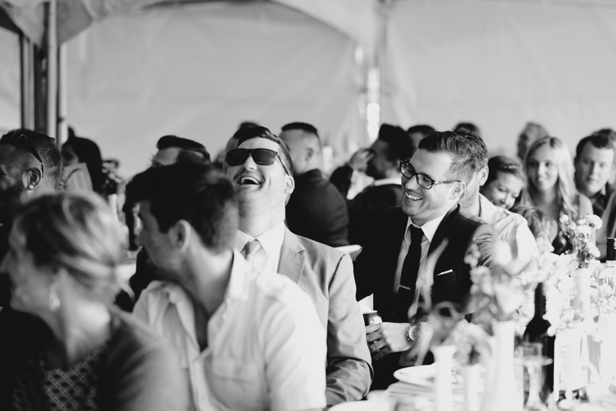 guests laughing during toasts under tent at shabby chic family farm wedding reception