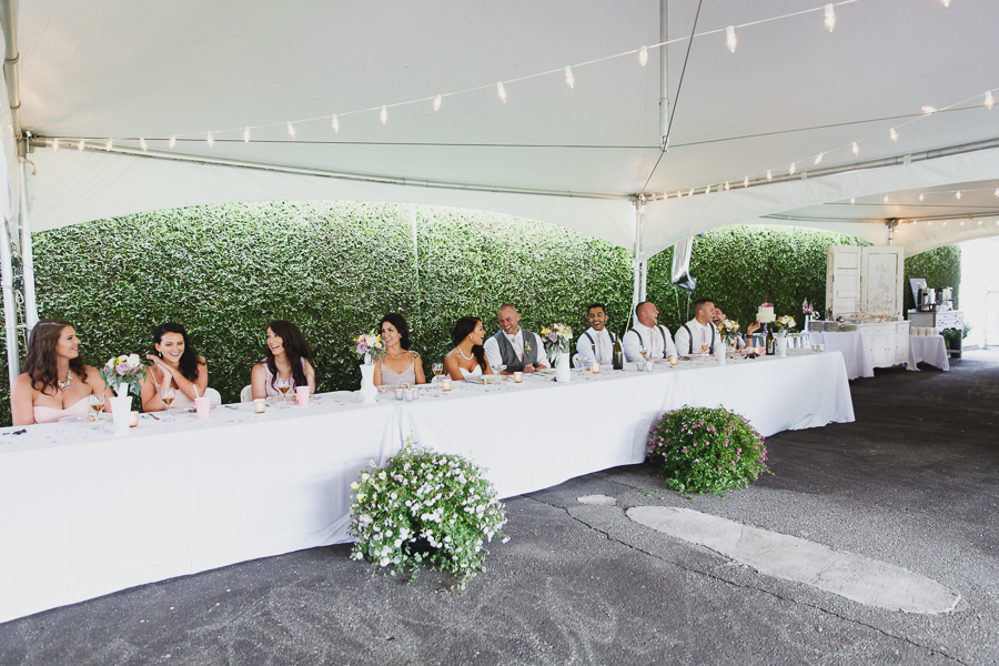 head table laughing during toasts under tent at shabby chic family farm wedding reception