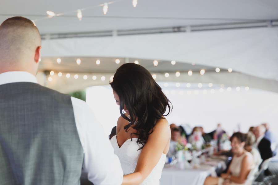 groom leading bride to dance floor under tent at family farm wedding for first dance