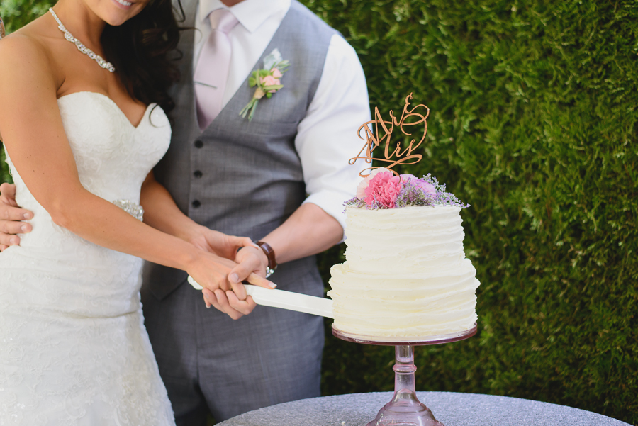 bride and groom cutting rustic wedding cake with wildflowers and Mr & Mrs cake topper