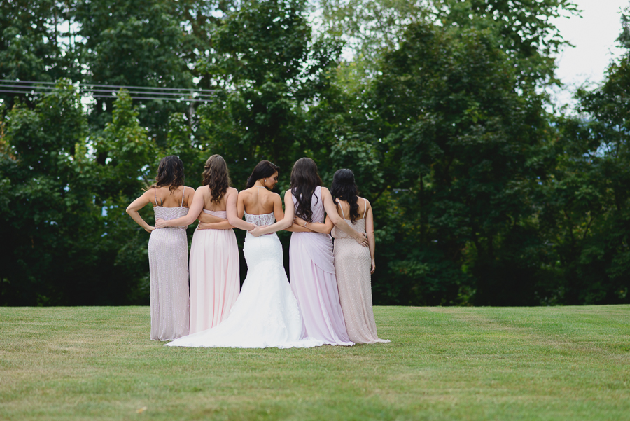 bride in sweetheart neckline lace fit and flare dress with bridesmaids in mismatched pink bridesmaids dresses with arms around eachother