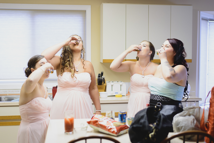 bride and bridesmaids in blush pink chiffon dresses drinking shots of Fireball