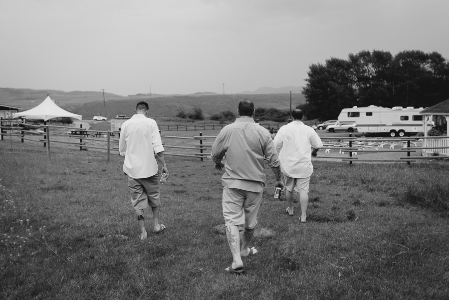 groom and groomsmen walking to wedding ceremony holding beer cans