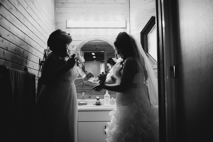 bride in ruffled dress, beaded sash, and veil putting on perfume with maid of honour before wedding