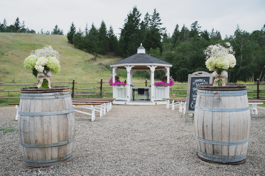 wine barrels with burlap and green and white florals at rustic gazebo wedding ceremony at Grandview Acres in Kamloops, BC