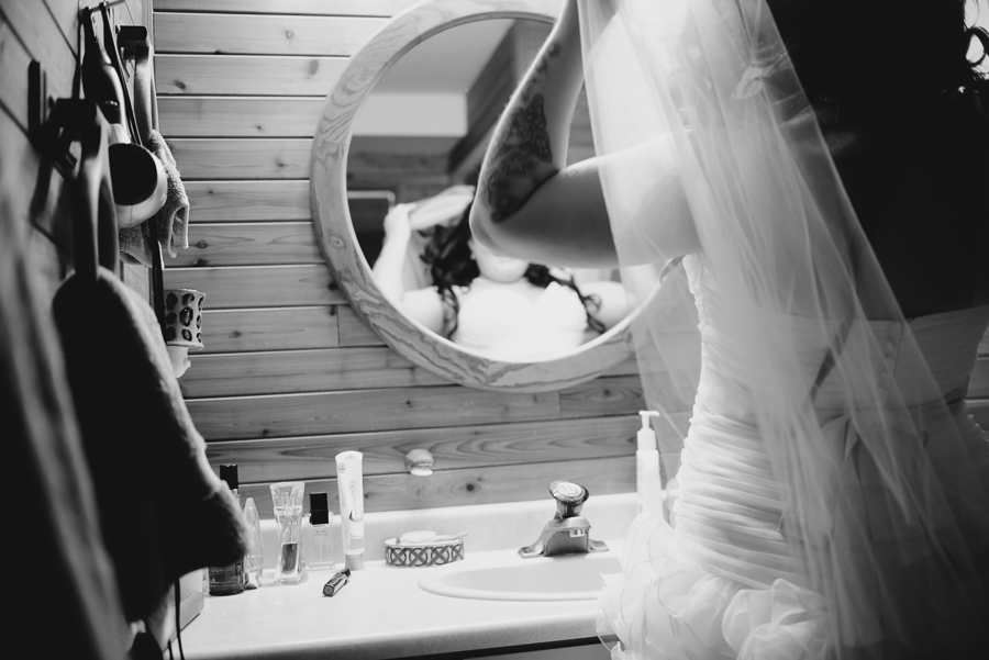 bride in button up ruffly dress fixing veil in mirror