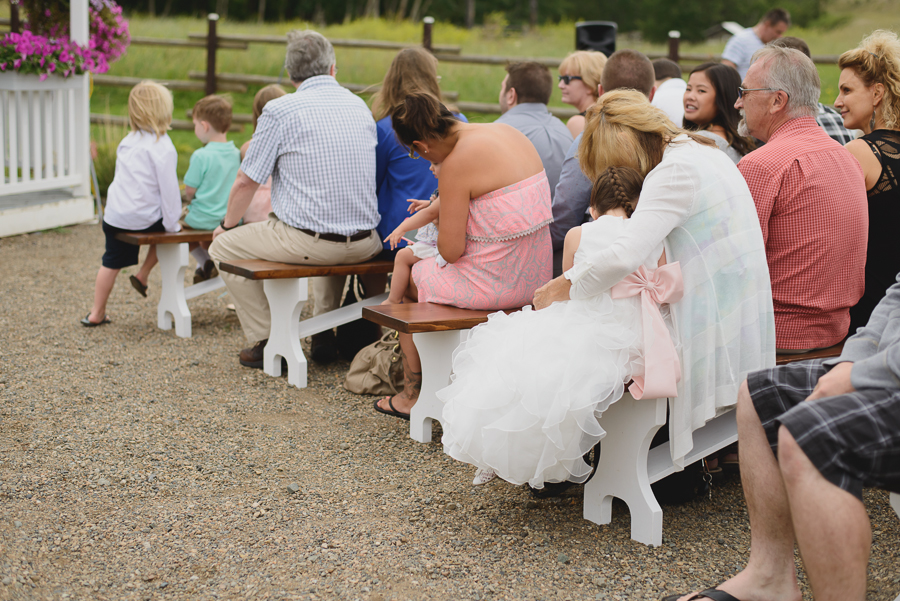 flower girl with ruffled dress and pink sash waiting for wedding ceremony to begin