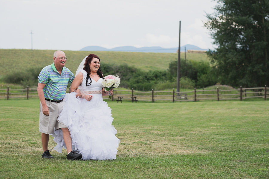 bride in ruffled one shoulder dress with pink beaded sash walking down aisle with father