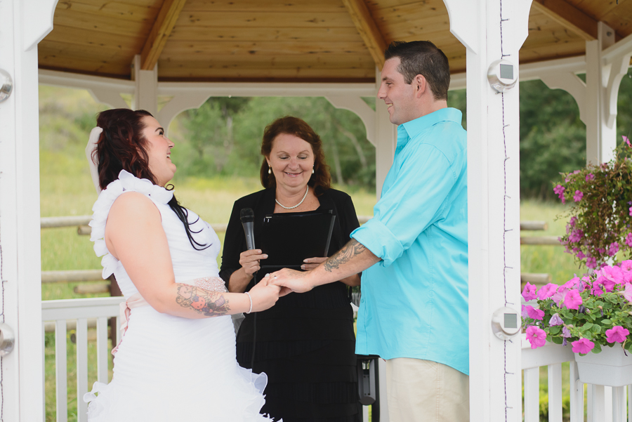 bride and groom with tattoos laughing during wedding ceremony