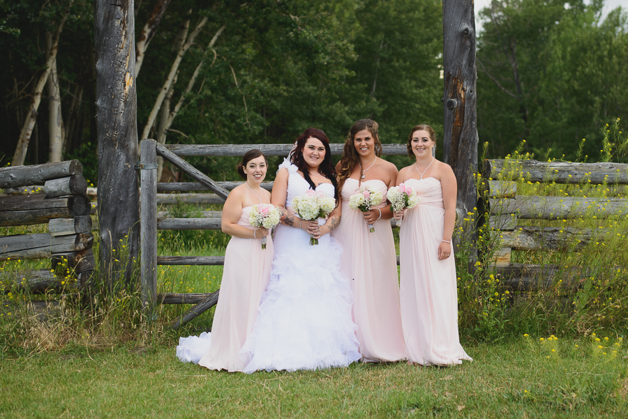 bride in ruffled one shoulder wedding dress with pink beaded sash with bridesmaids in long blush pink chiffon bridesmaid dresses in front of wooden fence at rustic wedding