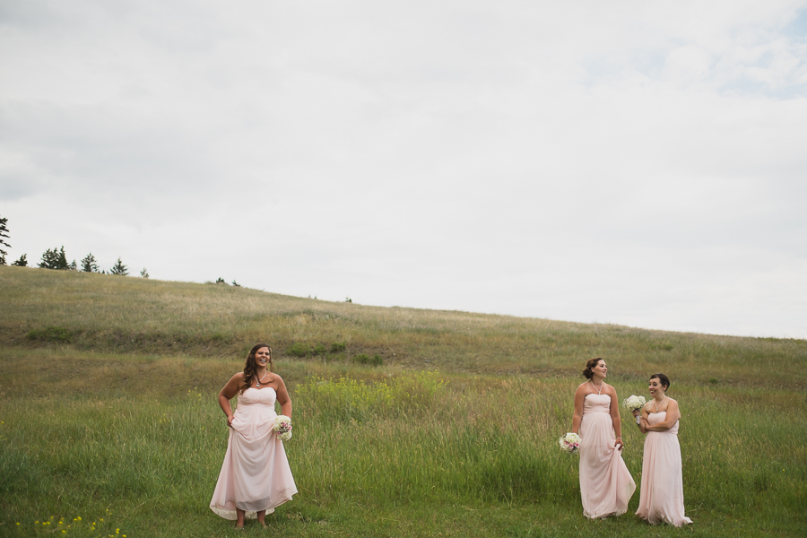 candid bridesmaids in long blush pink chiffon dresses laughing at rustic wedding