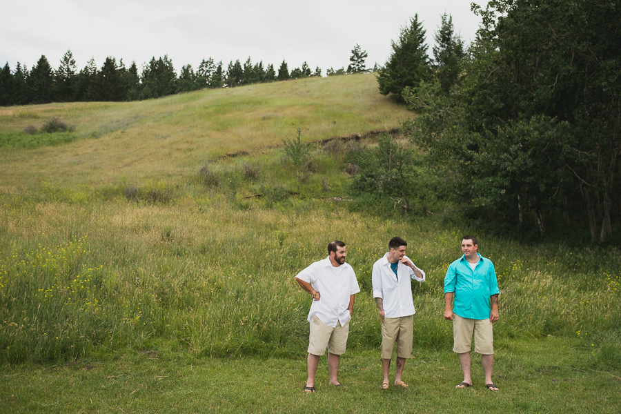 casual groom and groomsmen in button up shirts and khaki shorts after rustic wedding ceremony