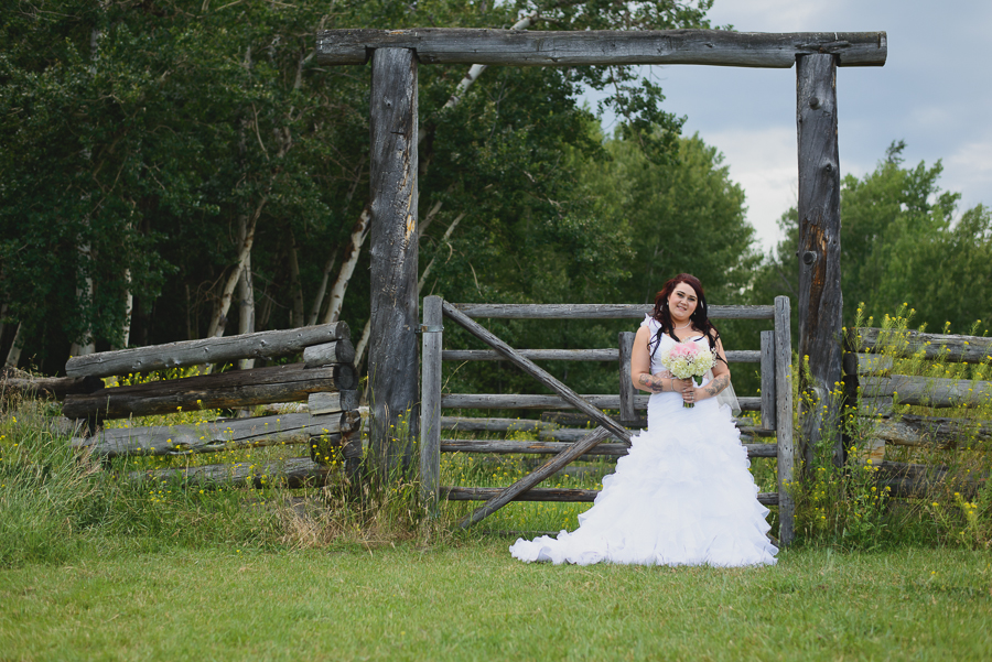 bride in ruffled dress with white and pink rose baby's breath rustic bouquet in front of fence at rustic wedding