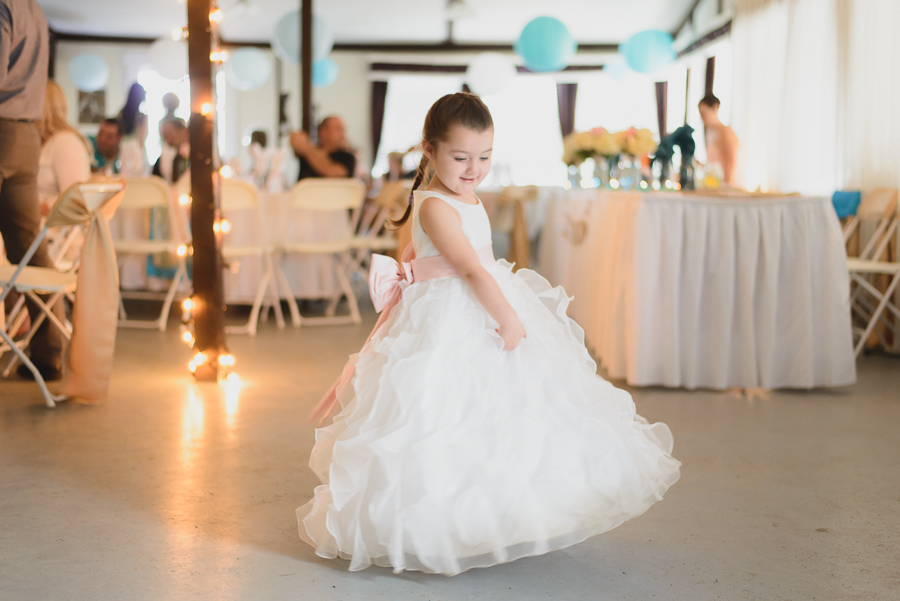 flower girl in ruffled dress with pink sash twirling at wedding reception