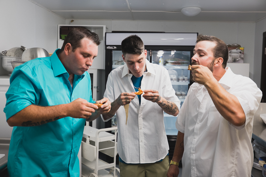 groom in casual turquoise button up eating chicken wings with groomsmen before wedding ceremony