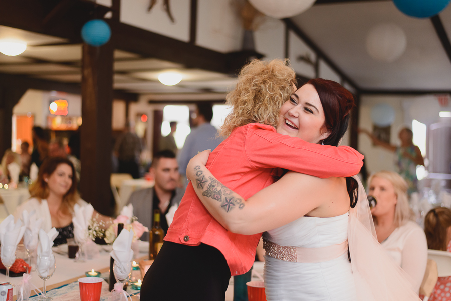 bride with tattoos laughing and hugging guests at wedding reception