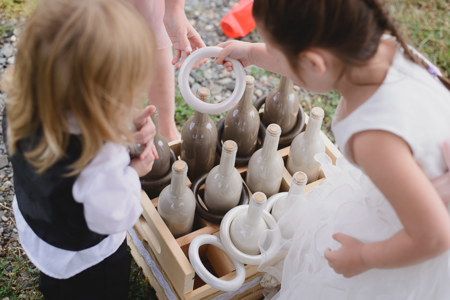flower girl and kids at wedding playing ring toss and lawn games during rustic wedding reception