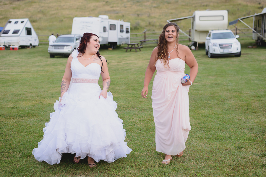 bride in ruffled one shoulder wedding dress with pink beaded sash walking and laughing with maid of honour in long blush pink chiffon dress