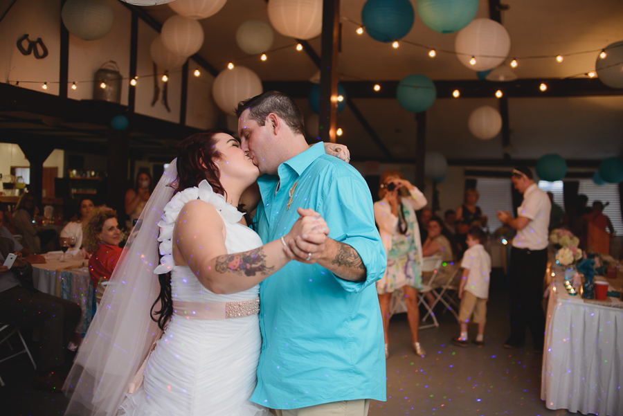 bride in one shoulder wedding dress with beaded pink sash kissing groom in casual turquoise cuffed shirt during first dance