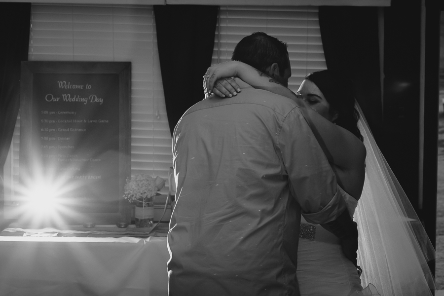 bride with long veil and groom in casual cuffed shirt dancing during first dance
