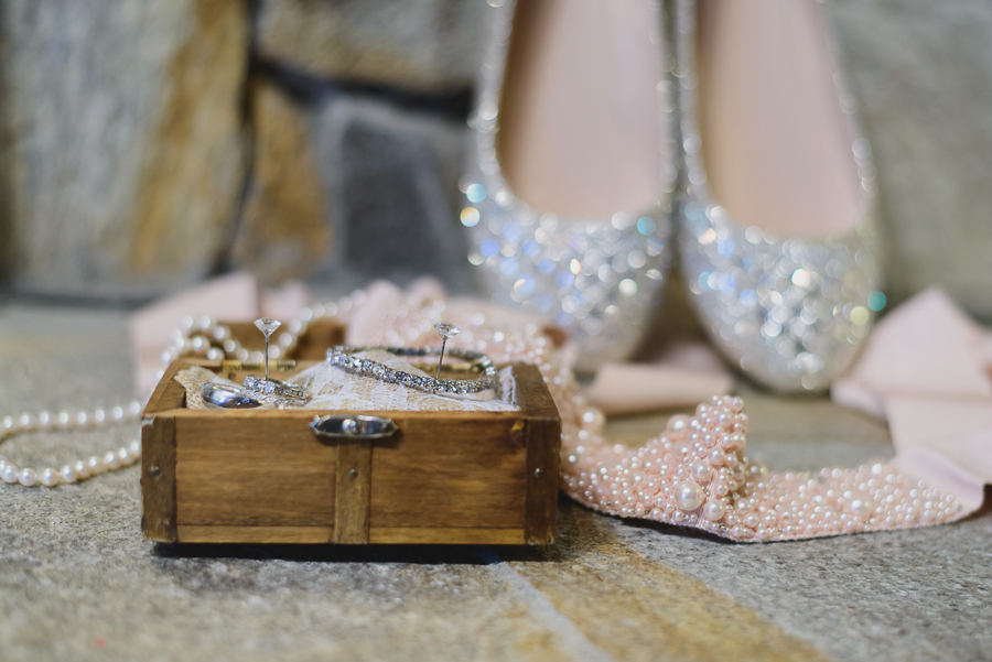wooden treasure chest with wedding rings and diamond bracelet, pink beaded sash, and sparkly wedding shoes