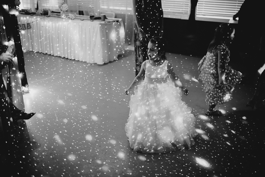 flower girl in ruffled dress with sash dancing in dance lights at rustic wedding reception